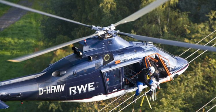 Installation of bird flight diverters by helicopter on a high voltage power line in Germany © RWE Netzservice