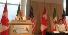 The Hon. Catherine McKenna, Environment Minister of Canada (standing at dias)